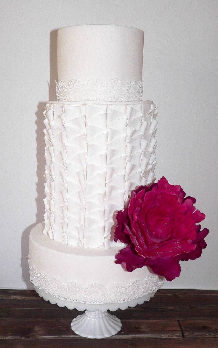 White wedding cake with lace and zig zag fondant pleats with a pink peony by Cake Corner Cakes Hobart.