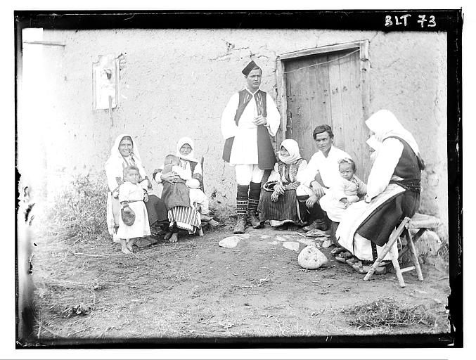 Grèce ; Macédoine ; Negocani (Νίκη-Φλώρινα)  (1916-1917) Légende Groupe familial macédonien posant devant la façade d'une maison Auteur photoBlanchet, Joseph