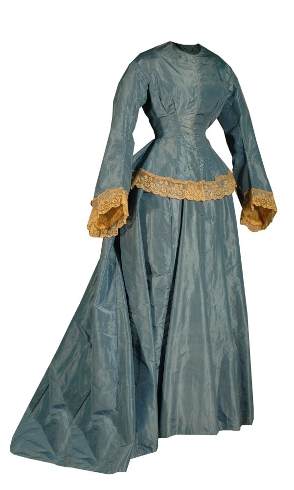 early 1870s Blue Taffeta wedding dress. Nellie Forbes married Sam Croft in this gown. It has a bustle and the jacket-style bodice, just becoming popular in the early 1870s, and is simply ornamented like many dresses from the previous decade. Only beige handmade lace trims the ends of the sleeves and the bottom of the bodice.