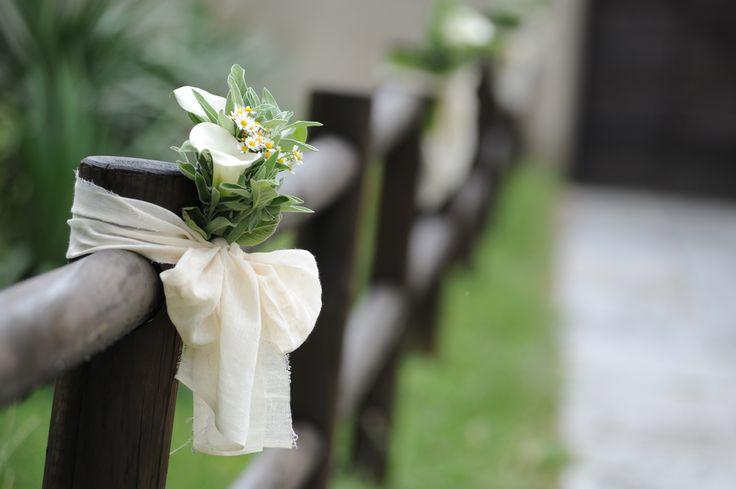L'ingresso per il rito civile è caratterizzato dalla semplicità delle calle e delle erbe aromatiche che si sposano con i tessuti in cotone grezzo e la staccionata in legno