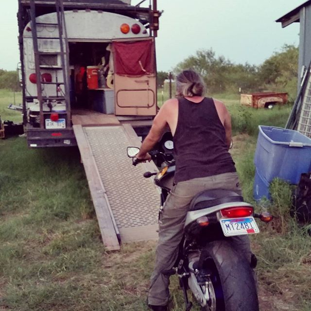 Loading up the motorcycle means riding it slowly in through the back door using a slide_out ramp salvaged from a U-Haul van. The ramp is part of the bus, but we carry 2x6s on the roof that we can attach to the sides of the ramp so there is room to place his feet. Years ago we didn't have the wood and Cobra would blast up the ramp without the safety net of the 2x6s. Now he's a little older and a little wiser.