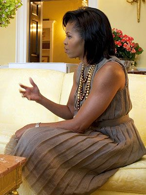 Ms. O wears a pleated linen dress from Rodarte. Mrs. Obama accented the feather-embellished design with three multi-hued strands of glass pearls from Erickson Beamon.