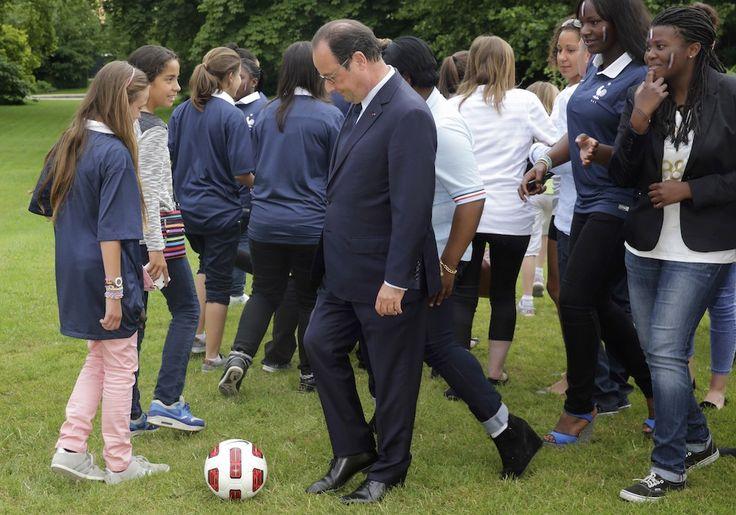 Politici e palloni: Il presidente francese François Hollande dopo aver posato per una foto con le squadre di calcio femminile Paris FC e Cosmos Taverny, a palazzo dell'Eliseo, Parigi, 30 giugno 2014 - Il Post