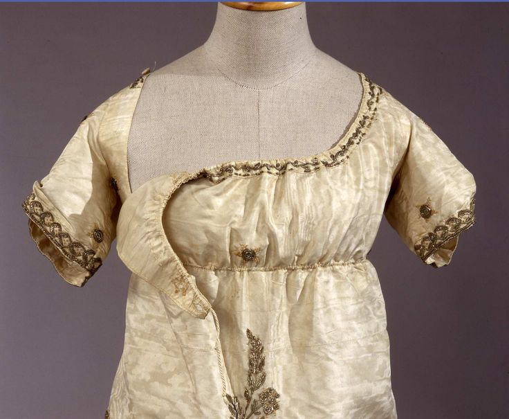 Early 19th entury, Italian. Gala dress in white moire silk, embroidered in silver gilt thread, with bib-front closure.