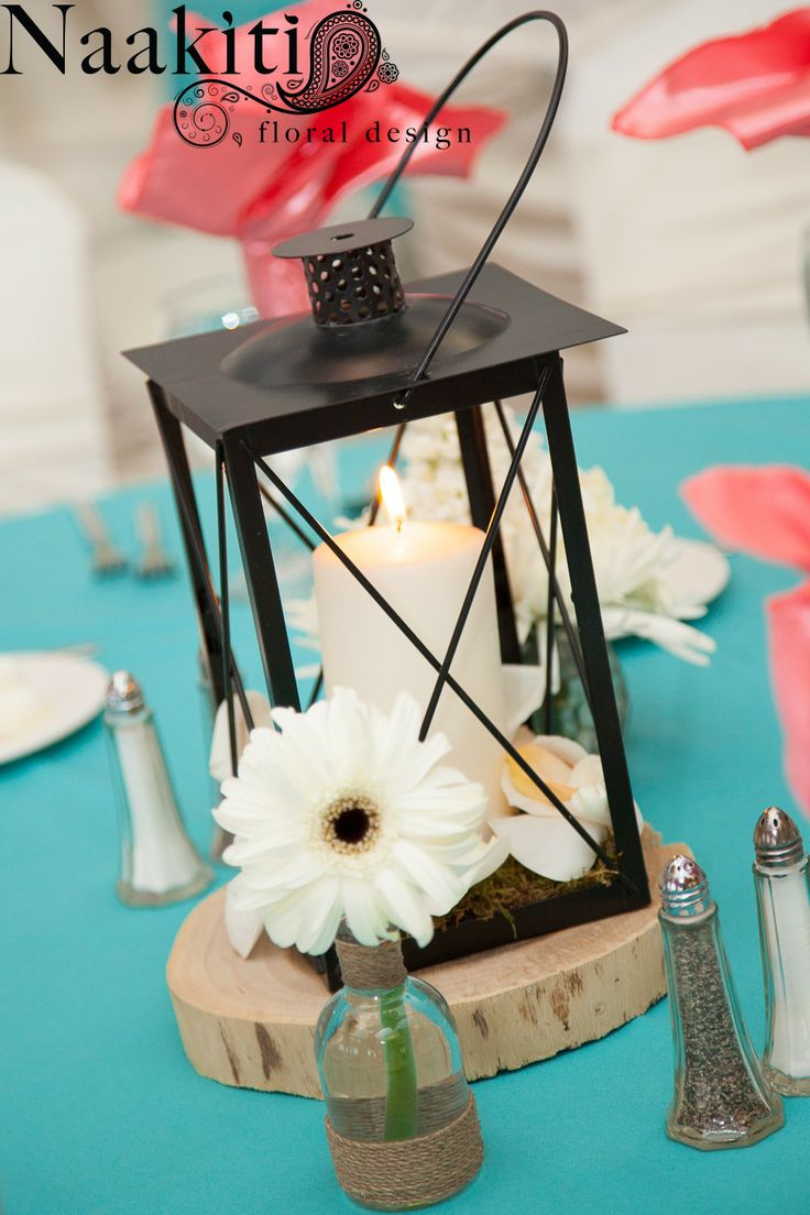 Black lantern on top of a wood stump with a white pillar candle adorned with white rose petals and white gerbera daisies in bud vases. #NaakitiFloral #Centerpieces #Weddings #LasVegasWedding #GerberaDaisy #Lantern #WoodStump #Budvase
