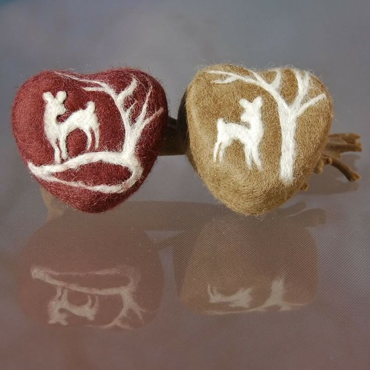Intricate detail of deer under a tree on felted heart soaps. In brown and tan.