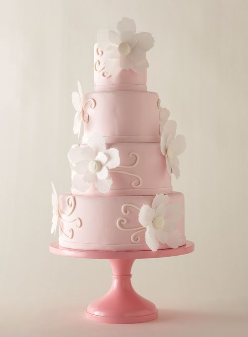 Jennifer Jones's blush-pink cake, which echoes the wedding invitation of one of her clients, walks just the right line between girly and elegant.  Fondant cake with paper-wafer flowers. Icing on the Top, Tulsa, OK; stand, Sarah's Stands.