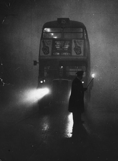 A man guiding a London bus through thick fog with a flaming torch, 1952