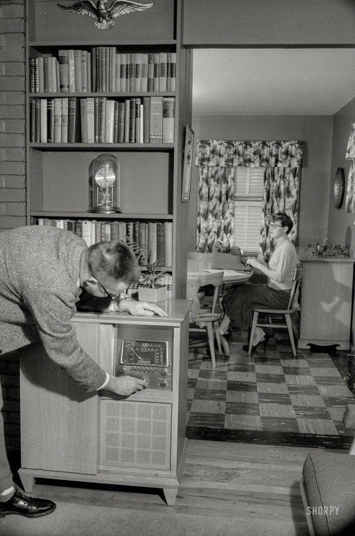 """Dick turned the volume up to 11 to drown out the sound of Mary's infernal pecking, while silently she plotted her revenge. Well, not really silently -- Mary was typing her plan at the kitchen table."" December 1957. Washington, D.C. ""Man tuning console radio while woman in next room types."" 35mm negative from the News Photo Archive."