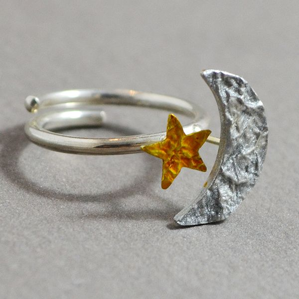 A pretty little moon and a bright little star on a silver ring. Both are hand painted with enamel and liquid glass. The ring is adjustable so it can fit any ring size.