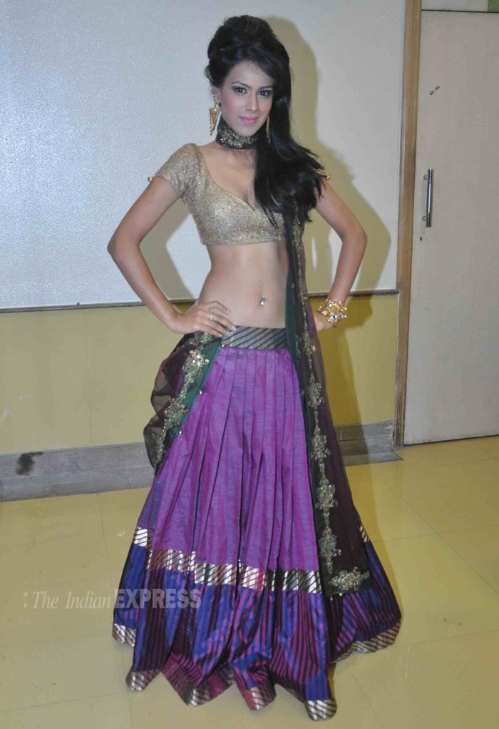 Nia Sharma strikes a pose in a gold choli blouse and deep purple lehenga skirt. at the WE WISH YOU PEACE Fashion Show. #Bollywood #Fashion #Style #Beauty