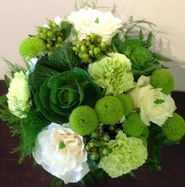A monochromatic floral bouquet is green and white tones. The roses look so wonderful with the button mums and decorative cabbage.