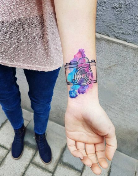 A simple camera outline by Kiss Katais accented with a big splash of color, making it more eye-catching thanthe average wrist tattoo. Click through for more stunning watercolor tattoo ideas.