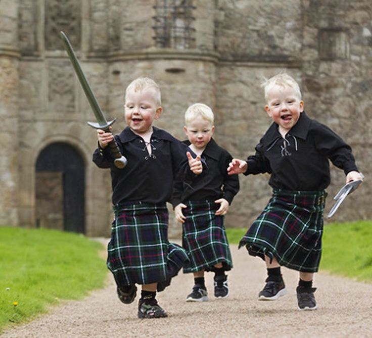 Three-year-old triplets Jack, Cameron and Liam Noble get in on the Brave act with kilts and toy swords. Tolquhon Castle, Scotland.