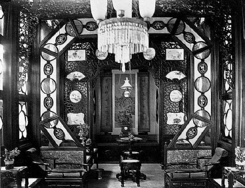 """An luxurious and ornately decorated opium smoking room, possibly inside one of the """"flower boat"""" pleasure craft that could be hired for a night of opium smoking on the Pearl River. The opium bed is at the back of the room. Circa 1880."""
