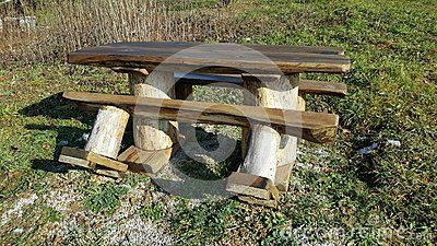 Heavy duty strong wooden outdoor table with two benches surrounded with tall dried vegetation and uncut green grass on sunny winter day