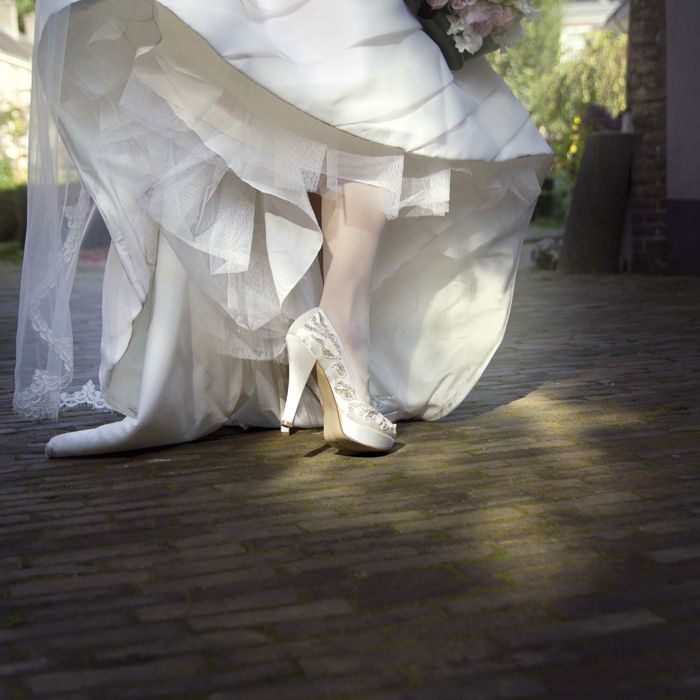 Witte bruidsschoenen met hoge hakken. Sophie Bruidsfotografie, sfeervolle trouwfotografie met een romantische en rauwe sfeer.