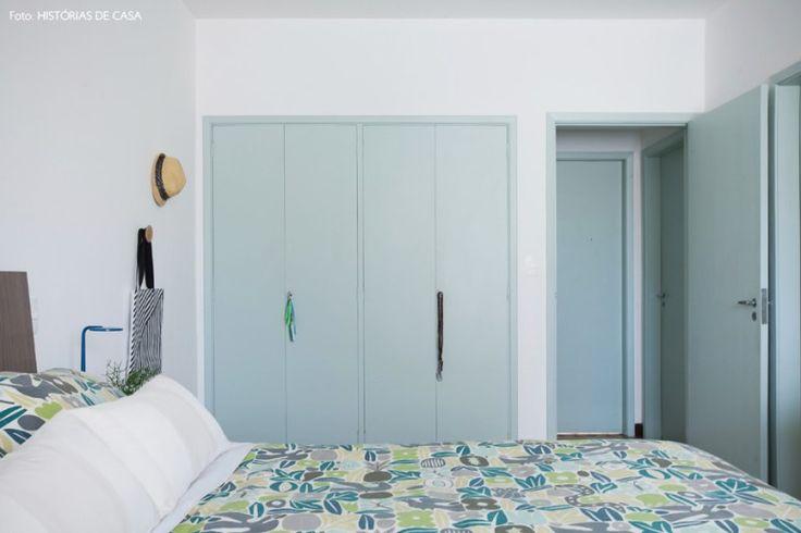 Quarto de casal com armários e portas pintados de verde menta e roupa de cama estampada.