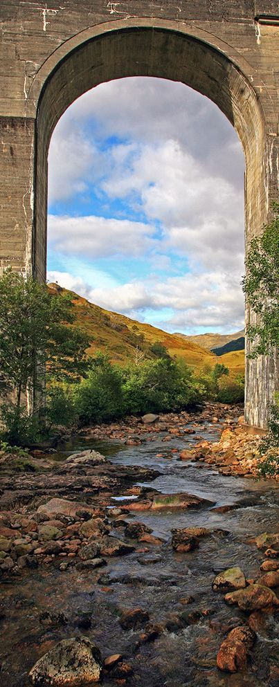 The river Finna gently flowing down to Loch Shiel with the famous Glenfinnan viaduct as a frame, Scotland