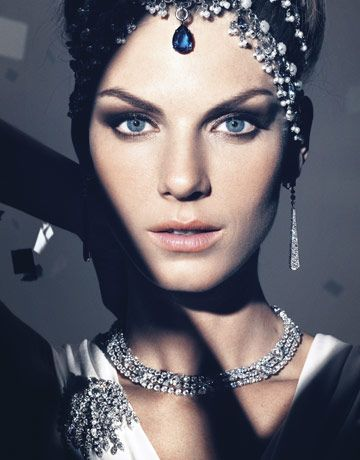 Angela Lindvall  					  						Up close and personal with major gems. Dress, J. Mendel. Headpiece,, Alexander McQueen. Earrings, necklace, and brooch, Cartier.