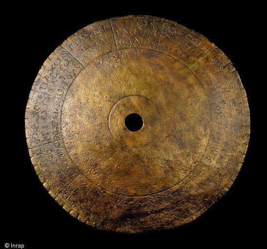 Ledisque astrologique de Chevroches (Nièvre), daté de la fin du IIIe s. de notre ère, 2001. Constitué d'une tôle en alliage cuivreux de 0,5.mm d'epaisseur percée en son centre, il présente un diamètre d'environ 65 mm. Sa courbure permet d'évaluer son diamètre d'origine à 100 mm..