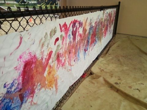 "Children's painting on fence, during ""Week of the Young Child""."