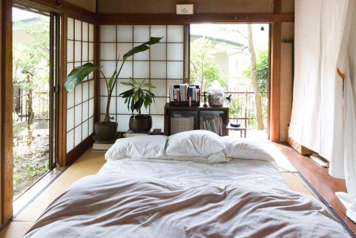 お茶室だった砂壁の和室。板の間は白いカーテンで仕切り、収納スペースに。