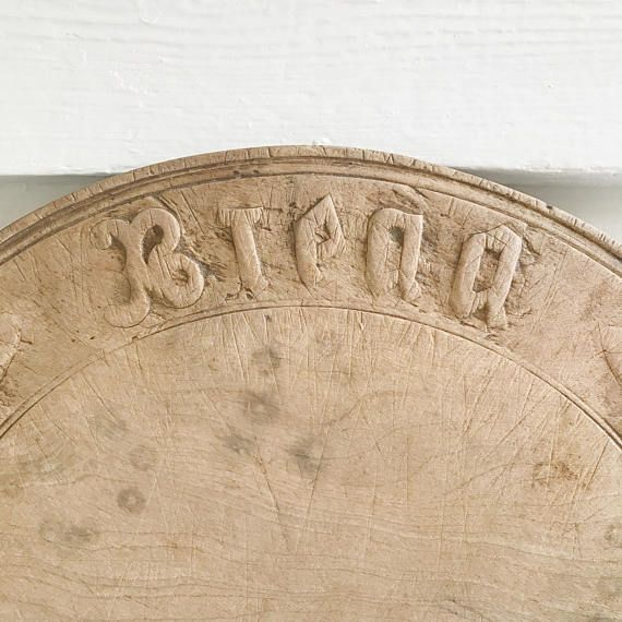 An antique round wooden bread board carved with the word 'Bread'. This beautifully smooth hand carved board is in very good condition considering its age and use. It shows its age in the form of cut marks and small chips around the edge that have long since been worn smooth. This is a very lovely piece indeed, both for use and display. It measures 29cm in diameter and is 2cm thick. Due to the difficulty in accurately calculating combined shipping rates I guarantee to refund all shipping…