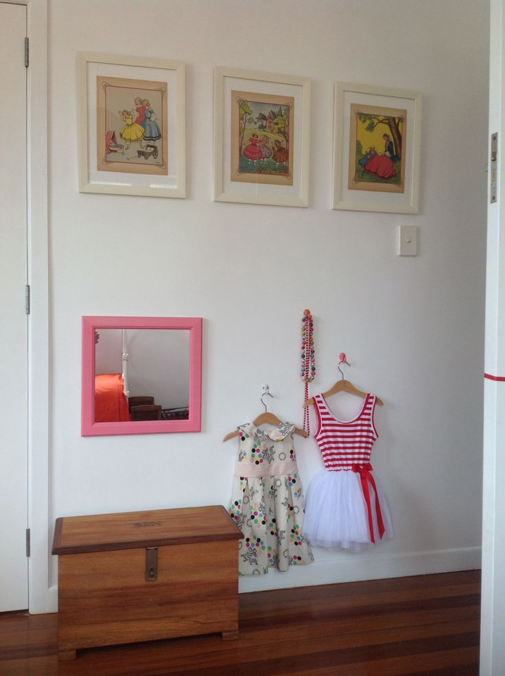 Dress up corner with mirror and painted hooks in soft orange, red, and pinks. 1950s Petites Filles Modeles prints found on a French flea market...