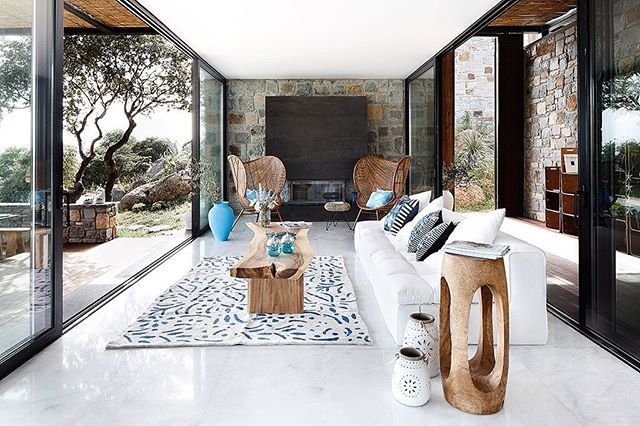 Joined to the #terrace via #slidingdoors this gorgeous #livingroom creates fluidity between indoors and #outdoors. The rough #stone wall of the exterior continues inside and is accompanied by a #monochrome scheme. #Design by Engel & Völkers Bodrum. Browse #homify for more amazing #interiors!  #interior #moderninterior #interiordesign #moderndesign #modernliving #modernlivingroom #couch #sofa #glass #fireplace #wood #timber #furniture #furnishing