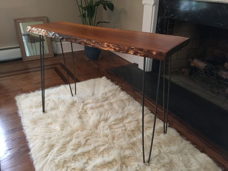 """Live edge cherry console table.  1. Got the raw slab from a lumber yard. About $20 and precut to about 40"""". 2. Cleaned it up and removed the bark gently chiseling with a hammer and putty knife. 3. Gave it a good sanding until smooth. Did it by hand to keep it a more uneven texture. 4. Finished it with 4 or 5 coats of Amber shellac (lost track of how many as I did it over a week). Sanded lightly with 220 grit sandpaper between each coat. 5. Bought the steel hairpin legs from Etsy for $80…"""