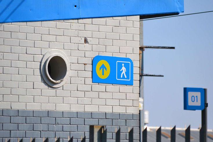 #blue #brick walls #bright colours #grey concrete #pedestrian #sign #signpost #train station #urban scene