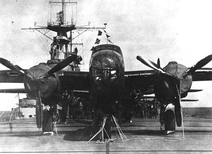 A crew member checks the lashings on his bomber aboard the USS Hornet, while behind him other crews check their planes in preparation for the Doolittle Raid on April 18, 1942.
