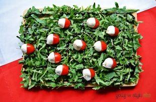Biało-czerwone przekąski z mozzarellą i pomidorkami koktajlowymi na rukoli