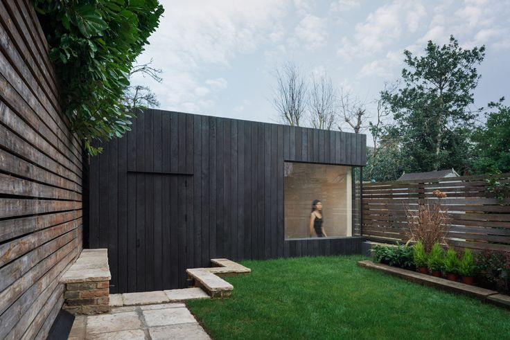 Eastwest Architecture has sunken a compact gym into the garden of a London home, featuring bright birch-lined interiors and a mirror wall.