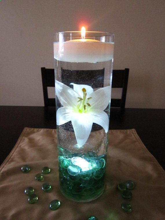 White lily is beautifully suspended in water with sea green marbles. The single vase is lit from within with one waterproof LED tea light. Perfect for your green theme wedding! The small floating candle is the perfect finishing touch.