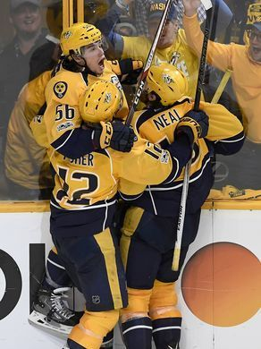 Predators left wing Kevin Fiala (56) is swamped by center Mike Fisher (12) and right wing James Neal (18) after scoring the game-winning goal in overtime to take the series to 3-0 in the first-round NHL playoff series late Monday night.  George Walker IV / The Tennessean