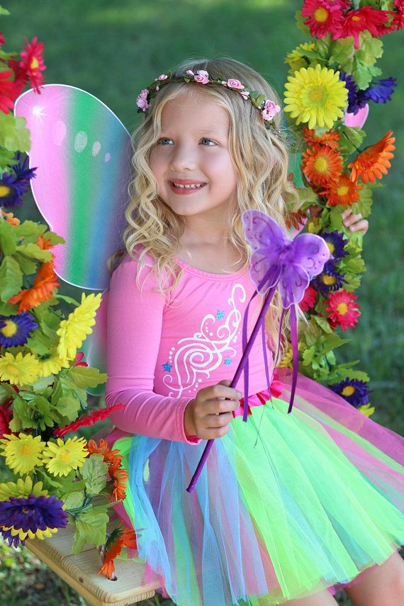 Dancing through the forest and spreading a little pixie dust, our Rainbow Fairy Costume is a must! Perfect for any little girl who believes in magic.   Just imagine her walking down the street with a basket in one hand to carry her candy galore and little wand in the other , waving and dancing around with a huge smile on her face and candy in her belly!   Full Rainbow Fairy Costume includes Fairy Leotard, Tutu , Flower Wreath Crown , and Wings/Wand. All pieces are made with high quality…