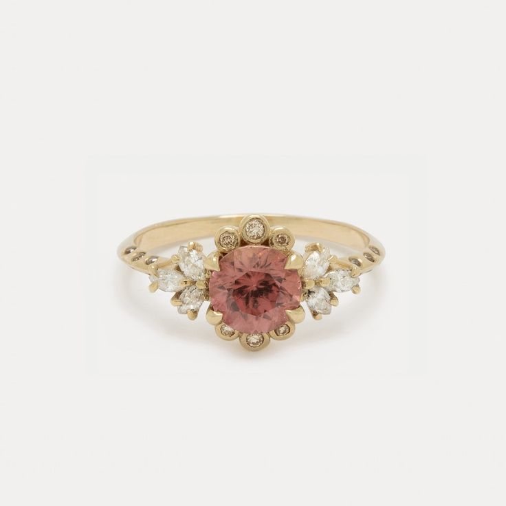 A statement cocktail ring that is an instant heirloom. This vision of a fine jewelry ring features a 1 carat faceted blush zircon surrounded by 6 round champagne diamonds and 6 marquise white diamond