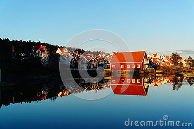 Traditional norwegian red rorbu. The estate of red wooden cottage on the Norwegian fjord surrounded by water, during an autumn sunset. Mirroring the blue sky and buildings in the water. Telemark region of Norway