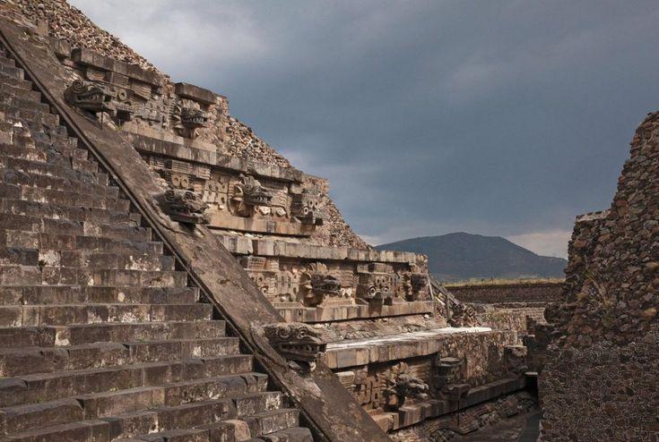"""Pirâmide de Quetzalcoatl,em Teotihuacán, a """"cidade dos deuses"""", México. Seu nome é formado pelas palavras quetzal, denominação de um pássaro da América Central e coatl, que significa """"serpente"""". É formada por 7 taludes ricamente decorados com cabeças representando serpentes emplumadas, além de conchas e caracóis. Interpretações recentes sugerem que Quetzalcotl era o deus patrono dos governantes e que a pirâmide estivesse relacionada à criação do tempo e do calendário."""