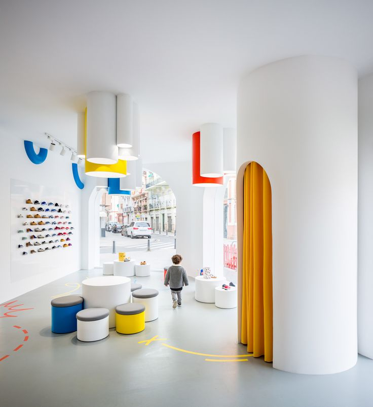 Spanish studio Clap has used arch-shaped cutouts and primary colours to create a playful children's shoe shop on a street corner in Valencia.