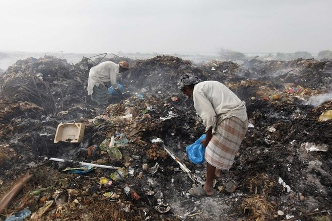 Men collected recyclables from a pile of smoldering garbage on the outskirts of Karachi, Pakistan, Monday.