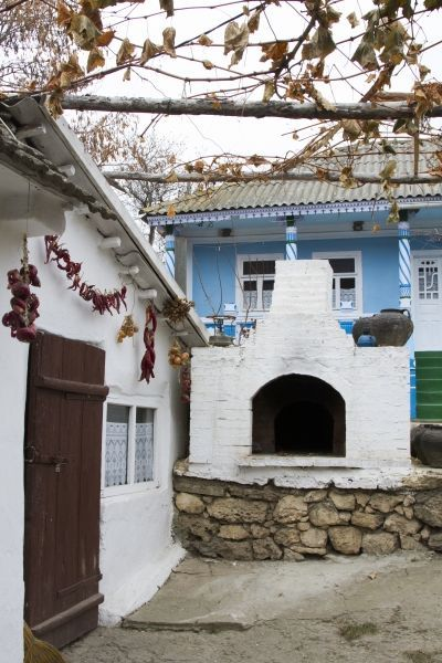 Beautiful blues, an outdoor fireplace, and chilis drying out.  This is a typical front yard in Moldova. Click through to see more Front Yards from Around the World. ~ReflectionsEnroute