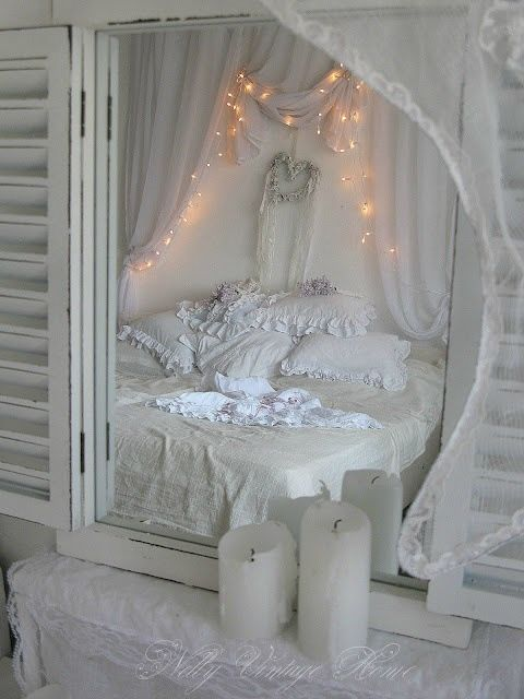 mirror with shutters reflects mussed shabby chic bed