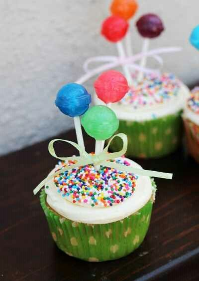 Fun and colorful cupcakes with lollipops on top - great for a carnival themed