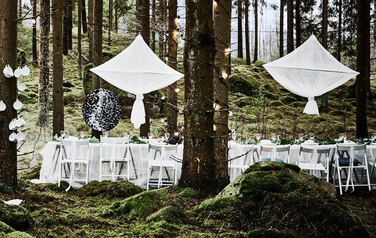 Banchetto di nozze in un bosco con sedie bianche, tovaglie ricavate da tende in pizzo e grandi decorazioni simili a candelabri appese a dei rami - IKEA