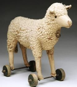 antiques price guide, antiques priceguide, toys, Germany, A Steiff Sheep or lamb on wheels. Wooly Steiff lamb stuffed with straw with shoe button eyes, little brass bell, original Steiff underscore button in left ear. It stands upon four wooden wheels.