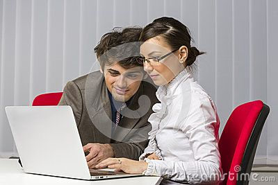 Two happy business partners working toghether on laptop in their office.
