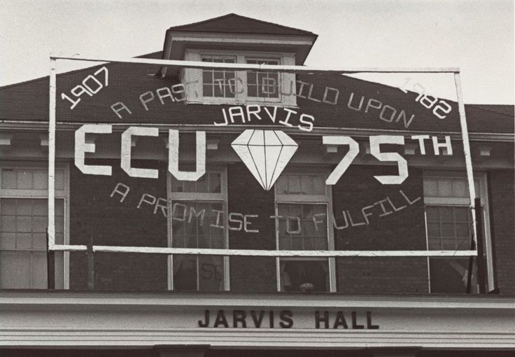 """View of Jarvis Hall with a sign celebrating the 75th anniversary of ECU. Sign says: """"1907-1982 A Past to Build Upon - A Promise to Fulfill, ECU - Jarvis - 75th"""""""